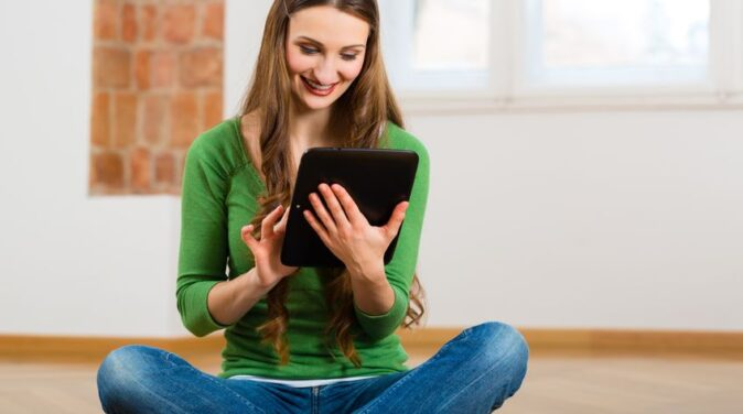 woman sitting on the floor with ipad on her hands