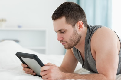 man using tablet while lying on bed
