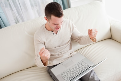 man sitting on the couch with laptop on his lap