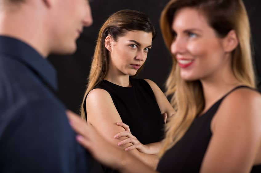 woman looking to the couple with her arms crossed