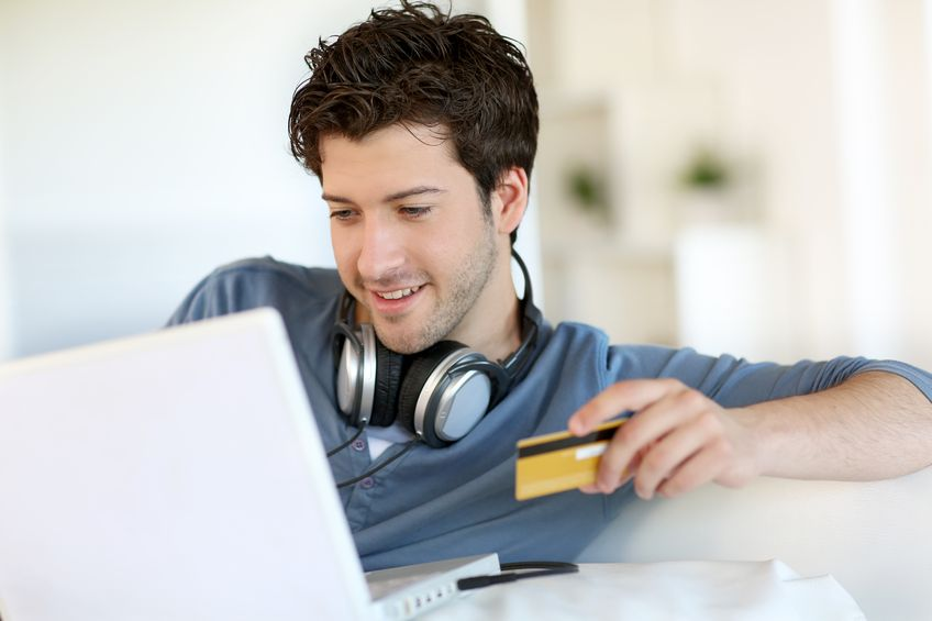 A guy wearing headphones and holding a credit card while looking at his computer