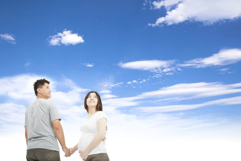 pregnant woman holding her husband and looking at the sky