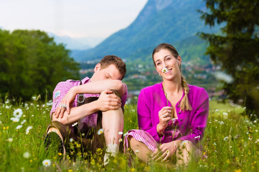 two young couple sitting on the grass both wearing purple colored clothes