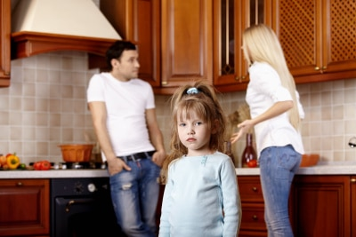 A child with her parents arguing at the back