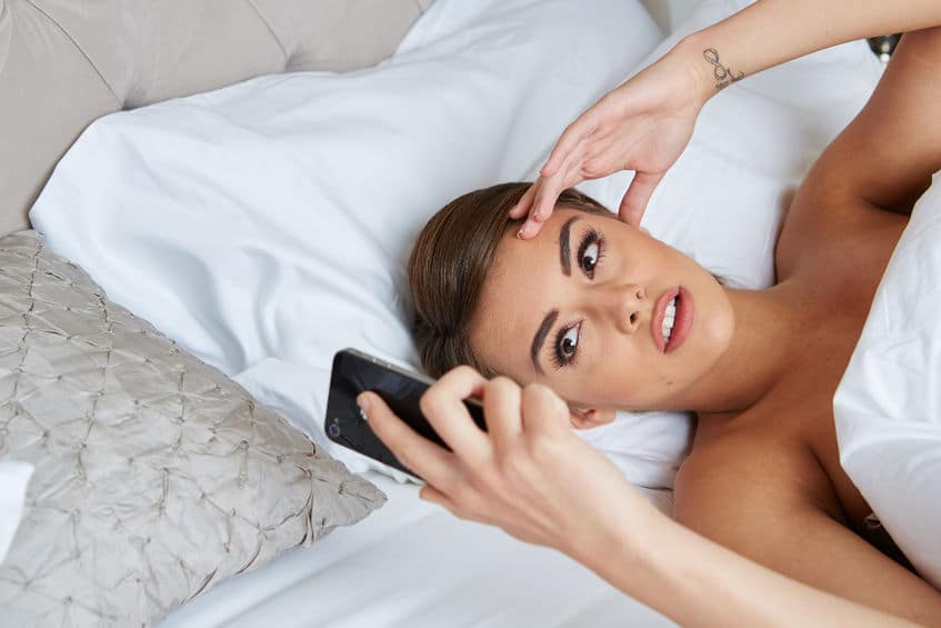 A woman lying down on bed looking to her phone