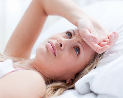 A confuse woman lying on the bed