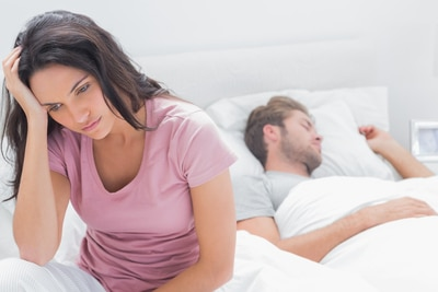 anxious woman in bed dating a new guy