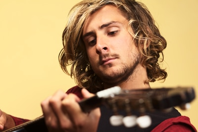 Young handsome Caucasian man playing the guitar (Selective Focus, Focus on the left eye)