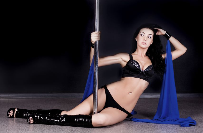 sexy woman wearing black two piece pole dancing