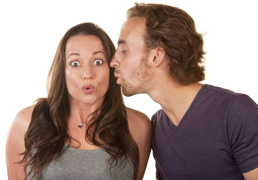 A man trying to kiss a woman on the cheek