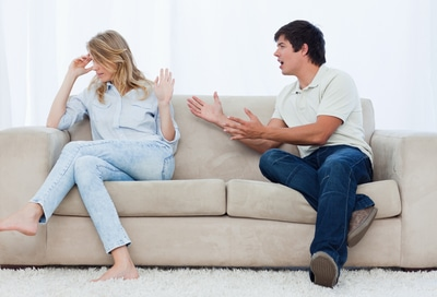A man sitting on a couch is having an argument with his girlfriend who has her head turned away