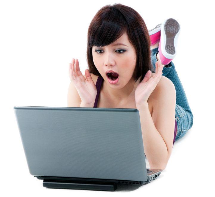 shocked woman using her laptop