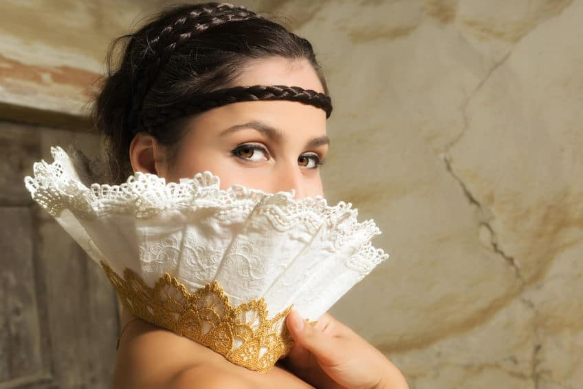 beautiful woman covering half of her face with a white fan like lace