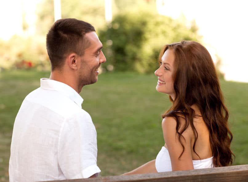 young couple smiling, looking at each other, sitting on a bench