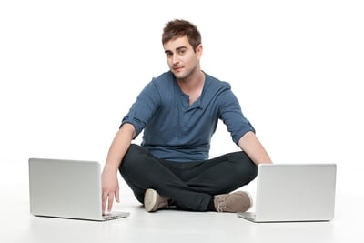 young man in between two laptops