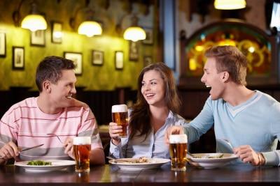 woman in between two men, having dinner while drinking beer