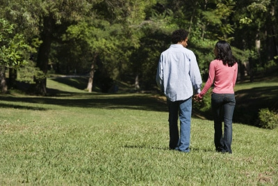 Couple holding hands walking and talking in park