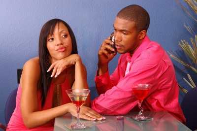 couple in martini bar, girl annoyed due to boyfriend taking on his phone