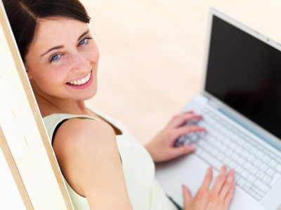 a happy young woman using her laptop
