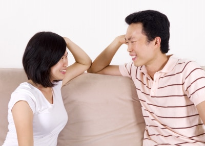young Asian couple sitting on the sofa, smiling at each other