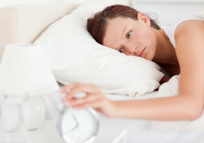 Red-haired woman lying in bed turning off alarm clock