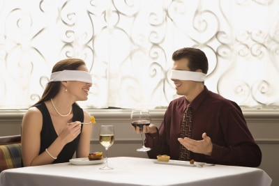 Couple dining wearing blindfolds.