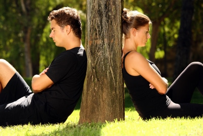 young couple separately sitting under a tree, being in conflict
