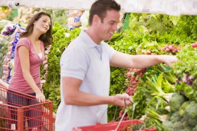young woman looking at a man buying products at the produce section
