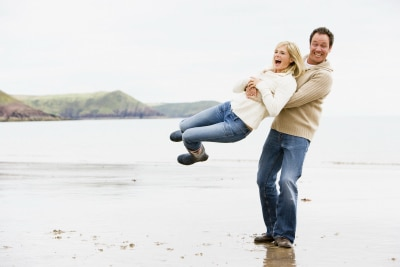 man happily carrying his woman at the beach