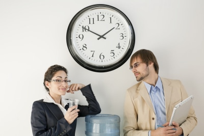 work colleagues talking under clock, drinking water