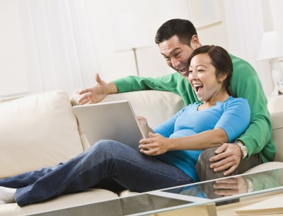 young couple sitting on the couch watching on their laptop, laughing