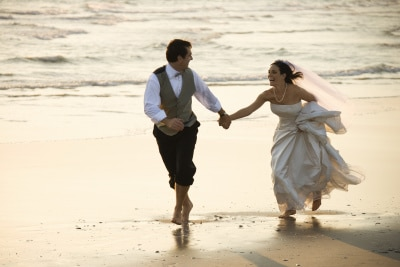 groom and bride running barefoot on beach
