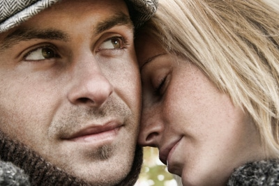woman's forehead on man's cheeks