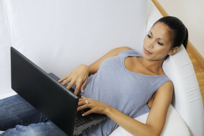 woman lying on bed while responding emails using her laptop
