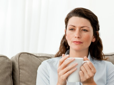 woman deeply thinking while drinking coffee