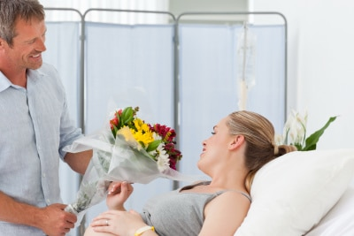 husband gives flowers to his wife at the hospital