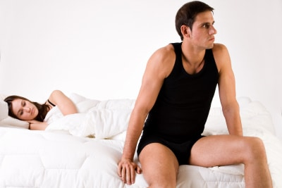 man sitting on the edge of the bed, woman looking at him