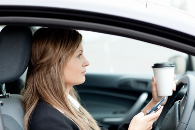woman stopping her car while sipping coffee, checking her phone