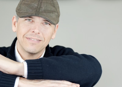 smiling confident man in a newsboy hat