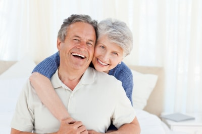 old couple looking happy in a hug