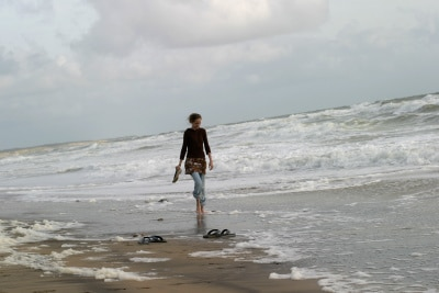 woman walking on the shore, alone