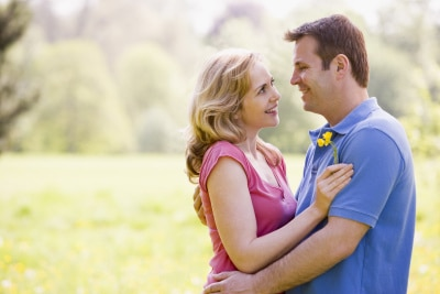 What You SHOULD Be Looking For in a Partner-Couple embracing outdoors holding flower smiling