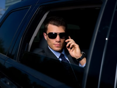 a business man on his phone riding a black car