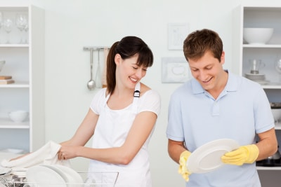 Lovers washing dishes together in their kitchen