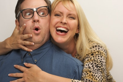 a grinning blonde woman embracing closely a man with an eyeglasses