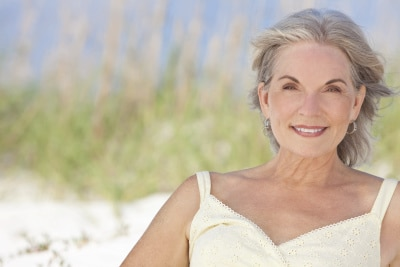 An attractive elegant senior woman sitting on a white sand beach with grass and a blue sky behind her.