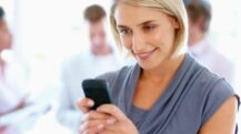 Closeup of beautiful woman reading text message with team in background
