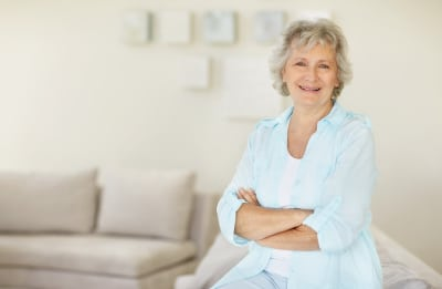 Portrait of a happy senior woman with hands folded relaxing on sofa at home