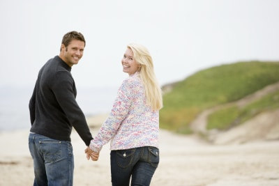young couple holding hands while walking on the beach