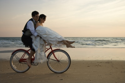 newly-wed couple riding a bicycle by the beach